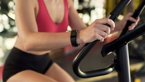 Healthy slim female wearing fitness bracelet riding exercise bike at sports club stock image