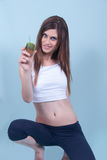 Healthy slim young woman, holding a straw in kiwi Stock Image