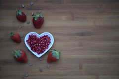 Healthy food photography image with fresh juicy shiny red pomegranate seeds in love heart shape dish on wood with strawberries Stock Photos