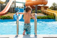 Healthy small kid enters blue swimming pool in water park with water tube slides in summer Royalty Free Stock Images
