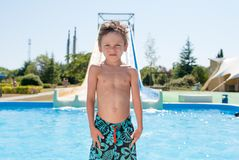 Healthy small kid in shorts in water park and blue fresh pool in summer day stock images
