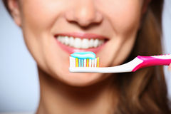Healthy smile. A picture of a toothbrush with toothpaste and a beautiful smile in the background Stock Image