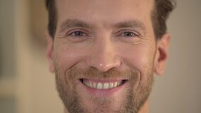 Healthy smile of handsome young man looking into camera, male face close-up. Stock footage stock video footage
