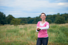 A healthy, smiling woman in fit wear with smart phone Royalty Free Stock Image