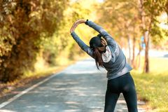 Healthy smiling woman warming up stretching her arms and looking away in the road outdoor. Asian runner woman workout before fitne stock photo