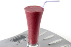 Healthy Smoothie. Refreshing healthy berry smoothie on top of weigh scales Royalty Free Stock Photography