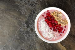 Healthy smoothie bowl with pomegranates, raspberries, coconut and granola Royalty Free Stock Images