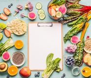 Healthy smoothie ingredients around clipboard with blank paper sheet on light table, top view, frame. Various fruits , vegetables. And berries with almond, chia royalty free stock photos