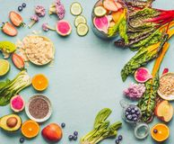Healthy smoothie ingredients on light table, top view, frame. Various fruits , vegetables and berries with almond, chia seeds and. Pine nuts for tasty vegan royalty free stock image