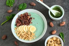 Healthy smoothie made from green raw ingredients. Cocoa nibs, banana and granola on a dark gray background royalty free stock photo