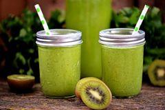 Healthy smoothies in mason jar from spinach, cucumber, celery, apple, parsley with olive oil. Food stock image