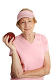 Healthy Snack. A senior woman dressed in pink for breast cancer awareness holding a red apple for a healthy snack.  Isolated on white Royalty Free Stock Image