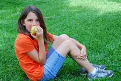 Healthy Snack. A young brunette girl takes a break from playing to have a healthy snack of an apple Royalty Free Stock Photography