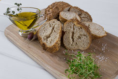 Healthy snack. Cereals bread, olive oil with herb spicy and garlic.Fresh cress salad. Stock Images