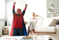 Healthy snack with cookies and milk. Superhero boy having an healthy snack with cookies and milk with his mother on background Stock Photo