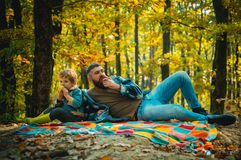 Healthy snack. Family picnic. Hipster bearded dad with son spend time in forest. Brutal bearded man and little boy eat stock images