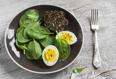Healthy snack - fresh spinach and an egg on a brown plate Stock Image
