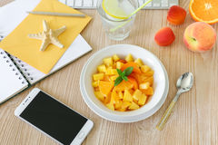 Healthy snack fruit salad of peach, apricot, orange in the workplace. Royalty Free Stock Photos