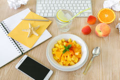 Healthy snack fruit salad of peach, apricot, orange in the workplace. Stock Photos