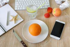 Healthy snack of fruits orange, peach and apricots at work. Stock Photography