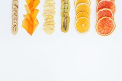 Healthy snack. Homemade dehydrated fruit chips on white background with copy space. Dry orange, grapefruit, mango, banana, kiwi. Diet food stock photo