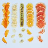 Healthy snack. Homemade dehydrated fruit chips on white background. Dry orange, grapefruit, mango, banana, kiwi. Diet food. square. Texture stock image