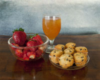 Healthy snack:juice,fresh fruits and muffins. Quick pause for an energetic snack: a bowl of fresh strawberries, mini chocolate chip muffins and a glass of fresh royalty free stock image