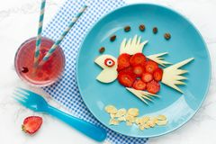 Healthy snack for kids - apple strawberry fish. On blue plate , fun food idea , animal shaped fruit plate stock photos