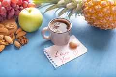 Healthy snack and love you text. Cup of aromatic coffee, heart shaped sugar pieces and a love you message on a math paper, surrounded by fresh fruits and nuts Stock Photos