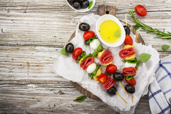 Healthy snack: mouth-watering kebabs on a picnic with tomatoes, mozzarella, salami, black olives, Basil, tortellini. Pasta on a cutting Board on wooden stock photography