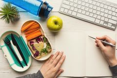 Woman eating healthy dinner from lunch box at her working table. Healthy snack at office workplace. Businesswoman working and eating organic vegan meals from stock photography