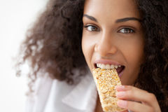 Healthy Snack. Smiling African woman eating a heathy cereal snack bar Stock Image