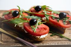 Healthy snack or Tomato, arugula, olives and creamy cheese on toast bread. Organic breakfast. Healthy snack or Tomato, arugula, olives and creamy cheese on toast royalty free stock photos