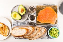 Healthy Snack with Wholemeal Bread Toasts, Avocado and Salmon. Table settings for the Healthy Snack with Wholemeal Bread Toasts, Avocado and Salmon Royalty Free Stock Photo