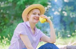 Healthy snack. Woman straw hat sit meadow hold apple fruit. Healthy life is her choice. Girl at picnic in forest on royalty free stock images