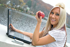 Healthy Snacking While at Work. A beautiful young blonde woman in a mobile business setting eating a red apple while using her laptop notebook computer royalty free stock photos