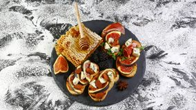 Healthy snacks with cheese and prosciutto, figs on wood board and napkin on a shale board. Breakfast, lunch food photo royalty free stock photos