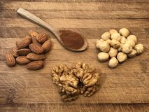 Healthy snacks and cinnamon powder on the wooden cutter board background. Healthy snacks made from hazelnuts, walnuts and almonds on the wooden cutter board stock photos