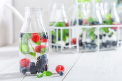 Healthy soda in bottle with raspberries, blueberries and blackberries stock image