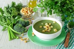 Healthy soup puree of broccoli, celery and herbs with croutons. Healthy soup puree of broccoli, celery and herbs with croutons in white bowl ready to eat next royalty free stock image