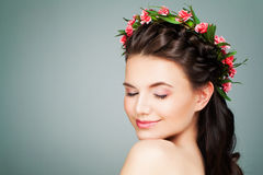 Healthy Spa Model Woman Relaxing. On Blue Background. Spa Girl with Natural Nude Make up, Wavy Hair and Summer Flowers Wreath Stock Image
