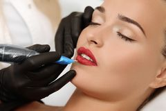 Permanent Make-up on her Lips. Healthy Spa: Young Beautiful Woman Having Permanent Make-up Tattoo on her Lips. Close-up royalty free stock images