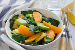 Healthy spinach, avocado and orange salad with ginger-vinegar dressing Stock Photo