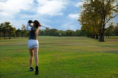 Healthy Sport. Asian Sporty woman golfer player doing golf swing tee off on the green evening time, she presumably does exercise. royalty free stock photography