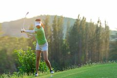 Healthy Sport. Asian Sporty woman golfer player doing golf swing tee off on the green evening time, she presumably does exercise. stock photos