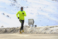 Healthy sport man running on asphalt road at snow mountains in trail runner hard workout in winter Royalty Free Stock Photos