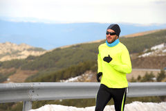 Healthy sport man running on asphalt road at snow mountains in trail runner hard workout in winter Stock Images
