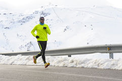Healthy sport man running on asphalt road at snow mountains in trail runner hard workout in winter Royalty Free Stock Images