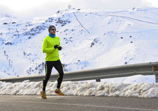 Healthy sport man running on asphalt road at snow mountains in trail runner hard workout in winter Stock Photos