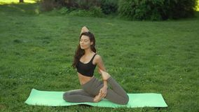 Healthy sports lifestyle. Woman practicing yoga outdoors in park. Healthy sports lifestyle. Woman practicing yoga performing yoga-asanas. Young attractive slim stock video footage